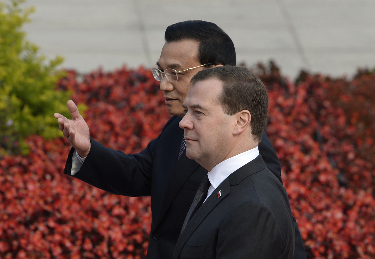 Chinese Premier Li Keqiang (L) speaks with Russian Prime Minister Dmitry Medvedev (R) during a welcoming ceremony at the Great Hall of the People in Beijing on October 22, 2013. AFP PHOTO / POOL / KOTA ENDO