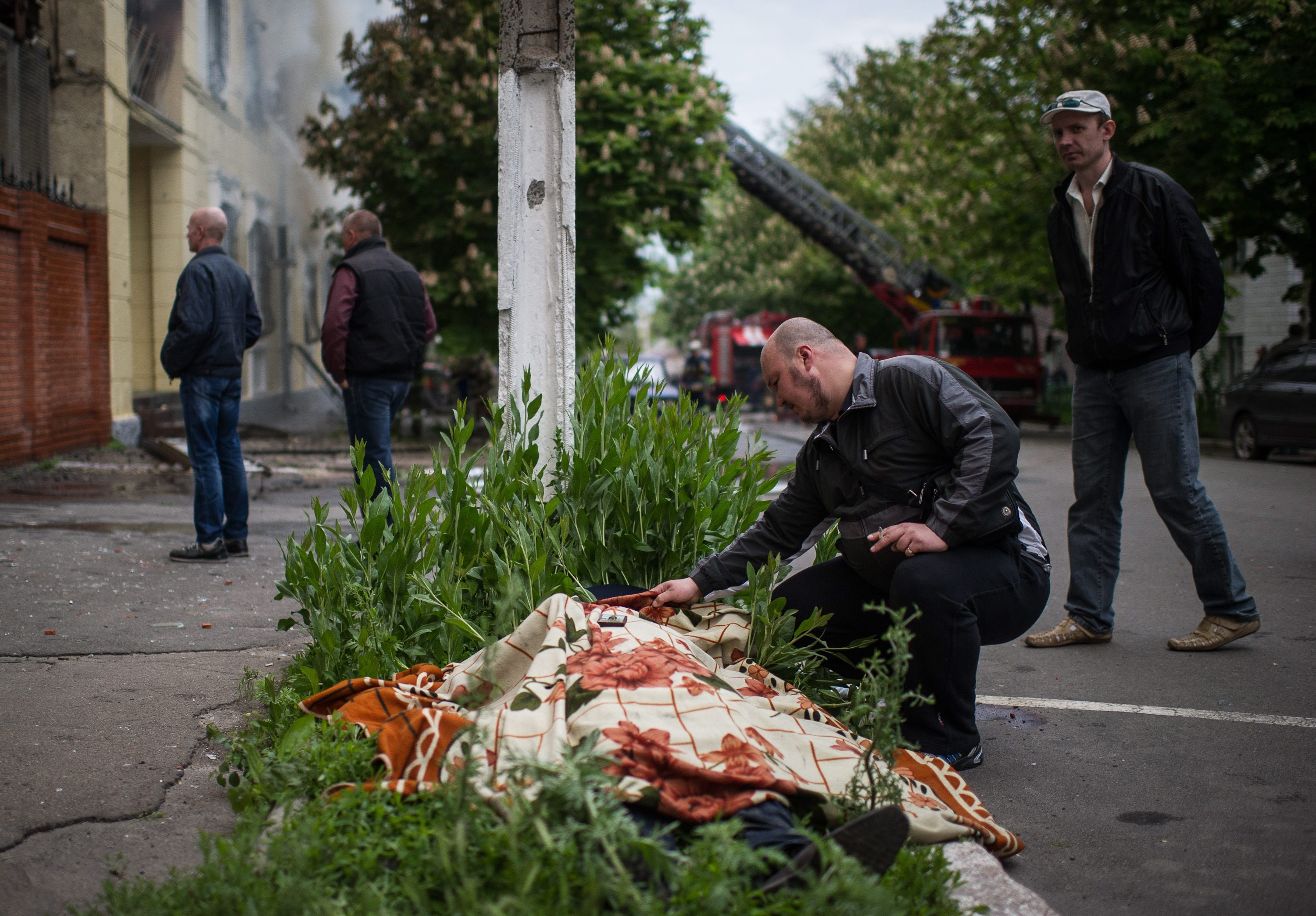 epa04198176 A man inspects the dead body near the Mariupol police station, Ukraine, 09 May 2014. Two eastern Ukrainian provinces will go ahead with a referendum on seceding from the country as planned this weekend despite Russian President Vladimir Putin's call for a delay, separatist leaders told Russia's Interfax news agency on 08 May. 'The referendum on May 11 will take place,' said Miroslav Rudenko, a separatist leader of the self-proclaimed Donetsk People's Republic. The secession referendum will let the three million residents of the provinces of Luhansk and Donetsk vote on whether they want to stay part of Ukraine. Ukrainians opposed to a split see it as a precursor to an eventual merger with Russia, as happened with Crimea in March.  EPA/ALEXEY FURMAN ATTENTION EDITORS: PICTURE CONTAINS GRAPHIC CONTENT