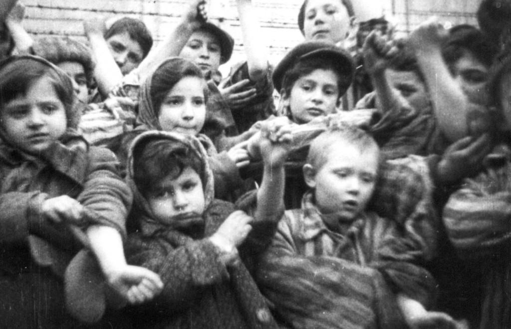 Дети, узники Освенцима, показывают следы отбора крови фашистами