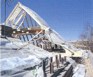 Рис. 11. Разобранную крышу накрывают целлофаном. В плиту перекрытия четвертого этажа загоняются огромные металлические швеллеры для восприятия распора