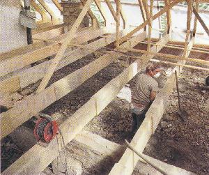Рис. 12. Рабочий стоит на перекрытии четвертого этажа, затяжка стропил на уровне плеч и головы