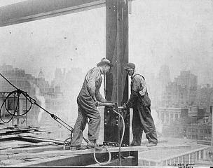 Рис. 17. Небоскребы Нью-Йорка. Рабочие затягиваю болты базы колонны. Рабочий слева стоит на доске, выдвинутой над пропастью. 1930 г.